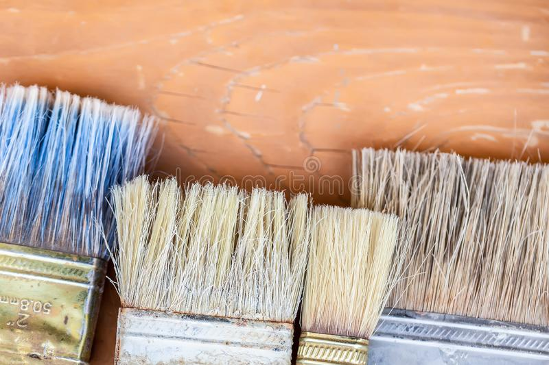 Close-up set of old used pant brushes on rustic wooden background. Vintage dirty paintbrushes. Copyspace tool work art white color artist object painter royalty free stock photo