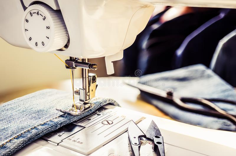 Close up sewing machine. Close up, sewing machine sew denim fabric at working space and blurred background royalty free stock photos