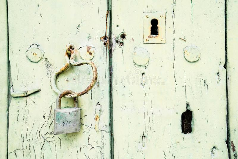 Painted wooden door with padlock and keyhole royalty free stock images
