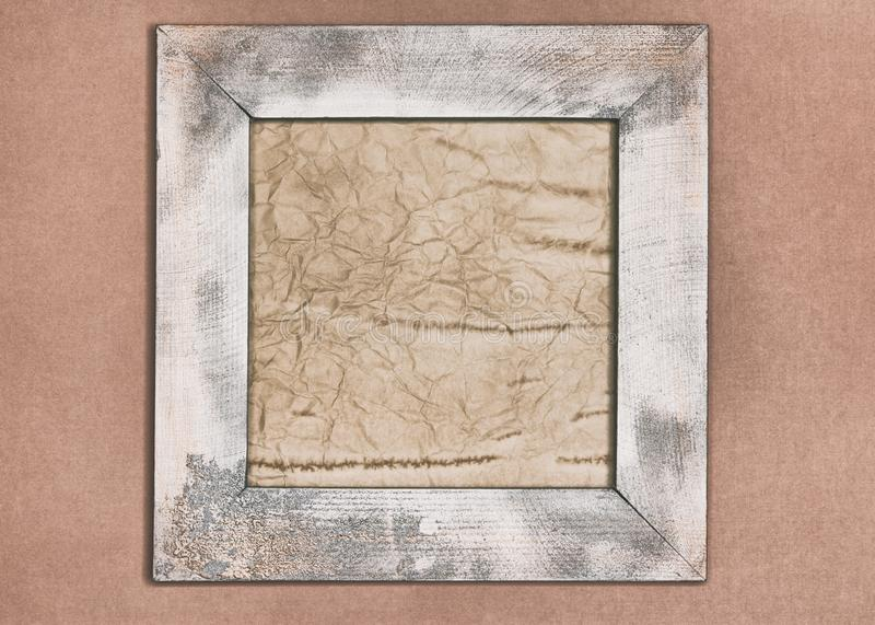 Aged paper in shabby wooden frame on old wallpaper wall. Close-up of shabby wooden frame with aged crumpled paper inside hanging on old wallpaper wall royalty free stock image