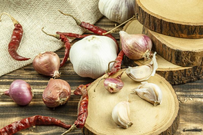 Close up of shallot, garlic, dried red chilli on wooden table background stock image