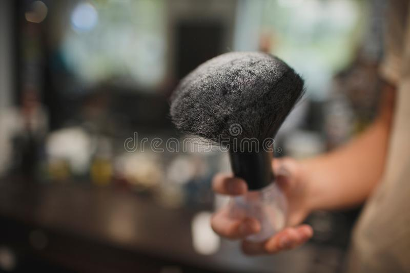 A close-up of a shaving accessory on a blurred background. A black brush in white talcum powder. Tools for cutting beard stock photography