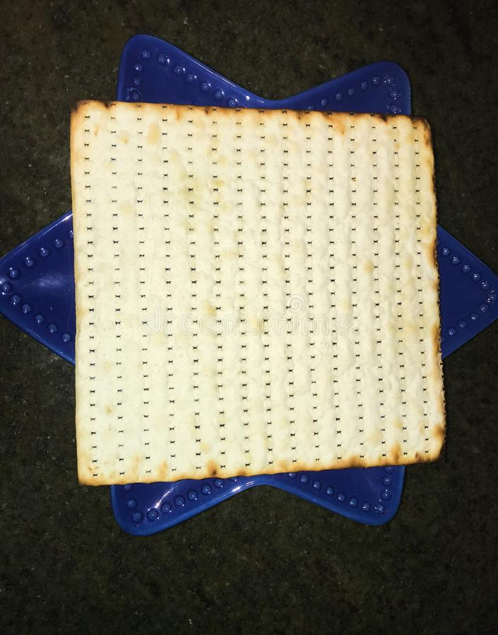 Close up a sheet of matzoh on blue plate stock photo