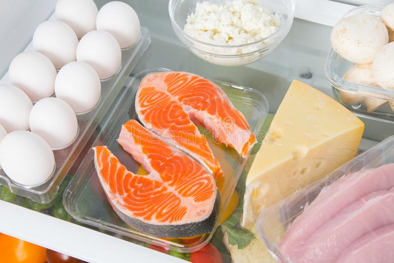Close-up shelf in the fridge where red fish, eggs, cheese, cottage cheese, mushrooms and meat royalty free stock images