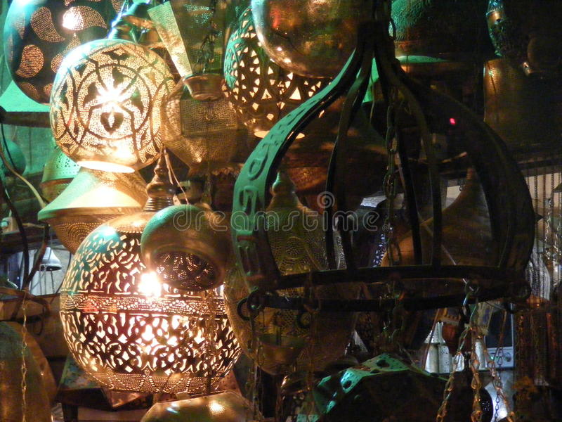 Close up of Shining lanterns in khan el khalili souq market with Arabic handwriting on it in egypt cairo. Vendor selling handmade copper oriental lamps ornaments royalty free stock image