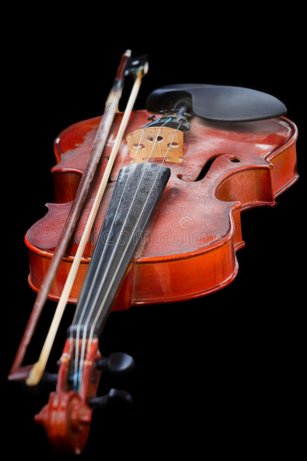 Close up of shiny violin on wooden table,. Isolated on black background, with clipping path stock images