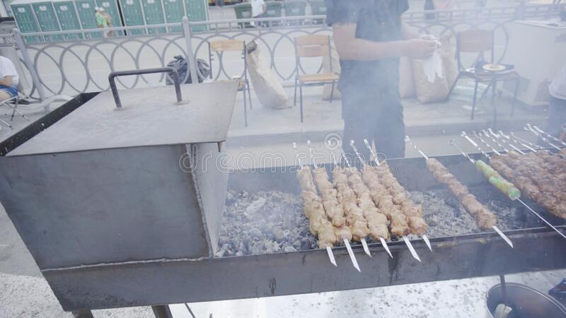 Close-up of shish kebabs prepared on grill. Art. Man professionally prepares kebabs on grill for sale. Grill is smoking. At time of frying juicy kebabs royalty free stock photography