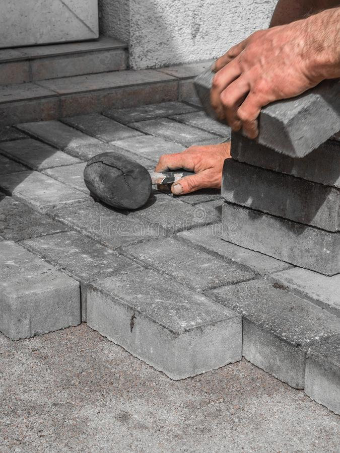Close up shit of construction worker paving the brick road royalty free stock photos