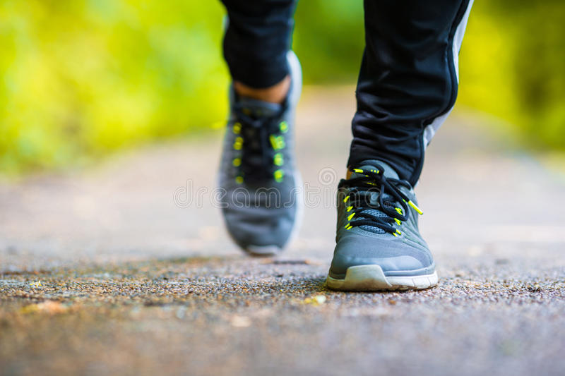 Close-up on shoe of athlete runner man feet. Closeup on shoe of athlete runner man feet running on road royalty free stock image
