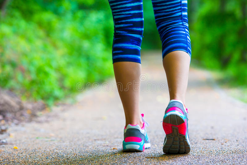 Close-up on shoe of athlete runner woman feet. Closeup on shoe of athlete runner woman feet running on road stock photo