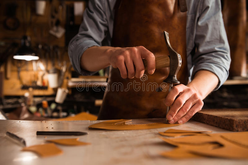 Close up of a shoemaker man working with leather. Using crafting tools royalty free stock photo