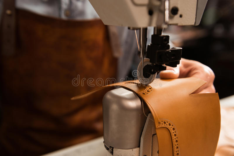 Close up of a shoemaker using sewing machine. In workshop stock image