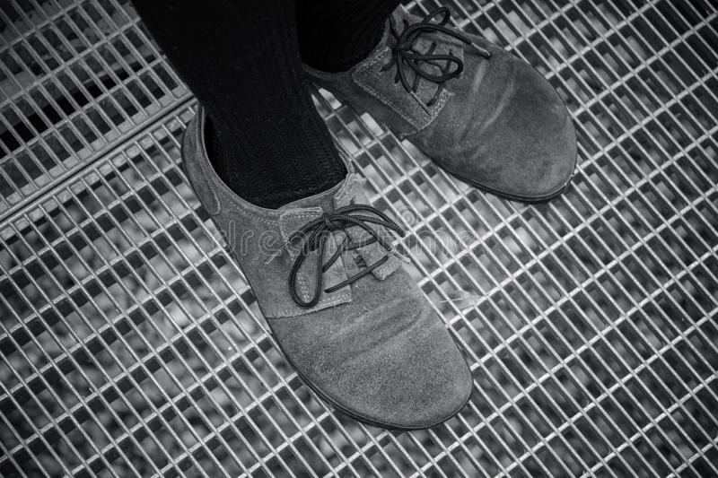 Close up on shoes while they stand on metal grate royalty free stock images