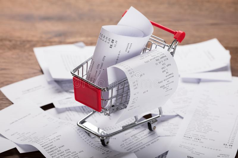 Shopping Cart With Receipts. Close-up Of A Shopping Cart With Bunch Of Receipts On Wooden Desk stock images