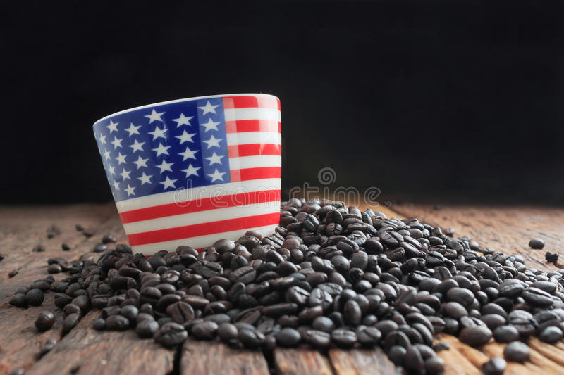Close up shot of america flag pattern ceramic cup on pile of dar. K roasted coffee bean and wooden floor with copy space, select focus on cup shallow depth of stock images