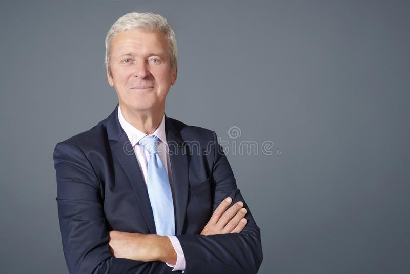 Senior businessman portrait. Close-up shot of an arms crossed senior businessman standing at isolated gray background royalty free stock images
