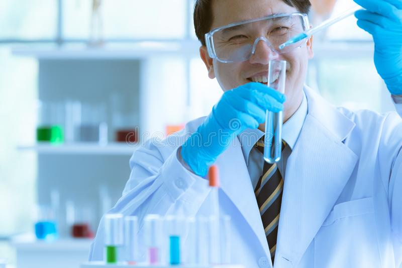Scientist dropping blue liquid into test tube stock photo