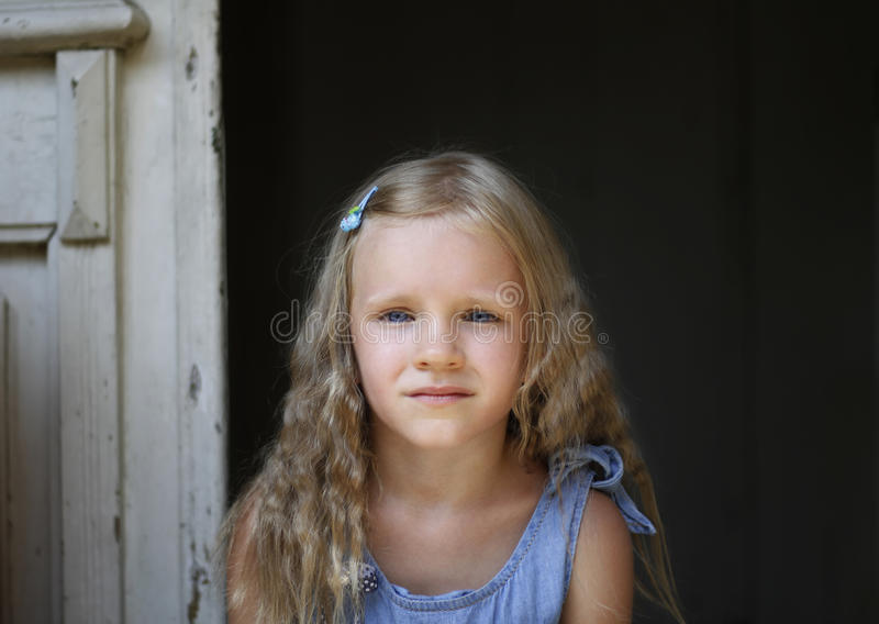 Close up shot of beautiful blonde little girl wearing jeans dress, looking at the camera royalty free stock images