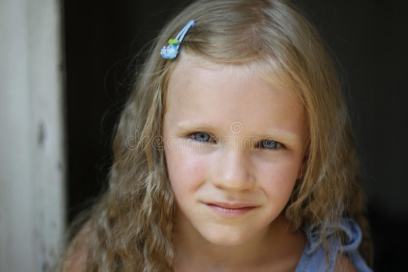 Close up shot of beautiful blonde little girl wearing jeans dress, looking at the camera royalty free stock photos
