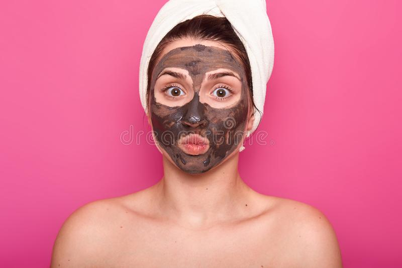 Close up shot of beautiful female, has chocolate mask on face, keeps eyes wide opened and lips rounded, poses with naked body, has stock photos