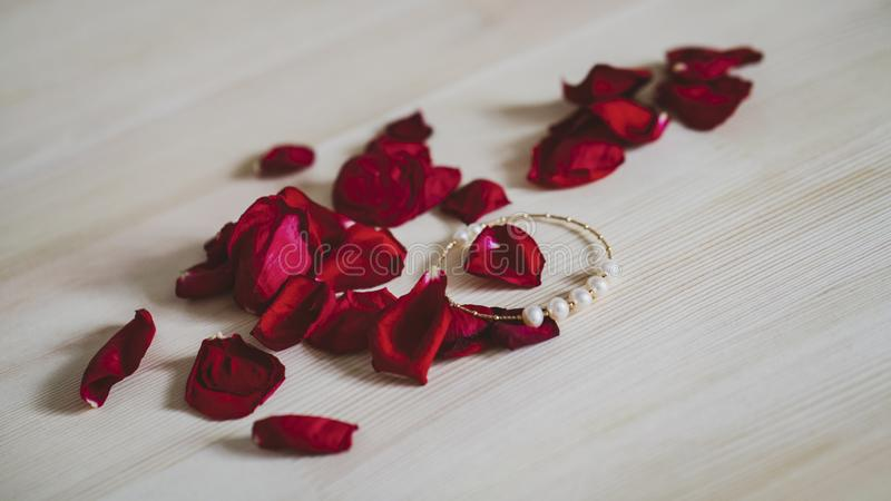 Close up shot of beautiful gold bracelet with pearls, with rose petals in the background.  royalty free stock images