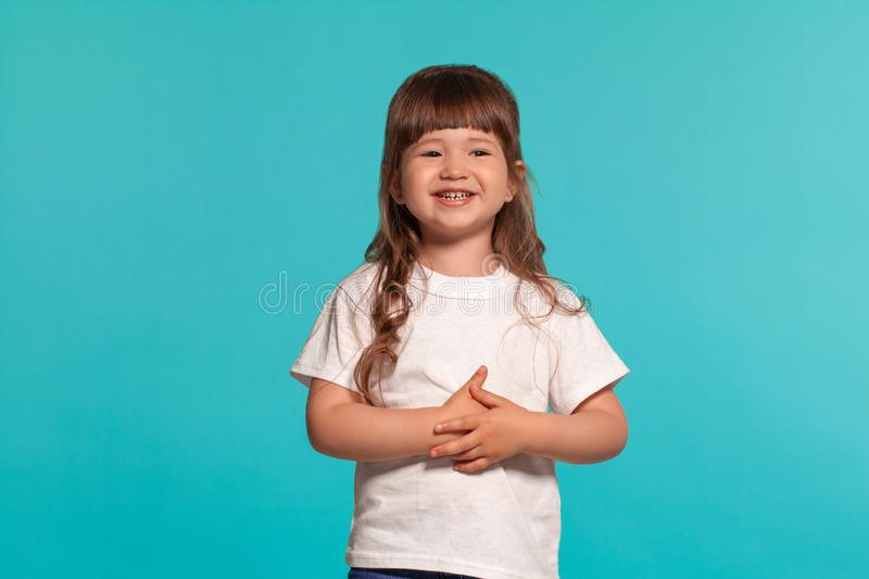Beautiful little girl wearing in a white t-shirt is posing against a blue studio background. stock photos