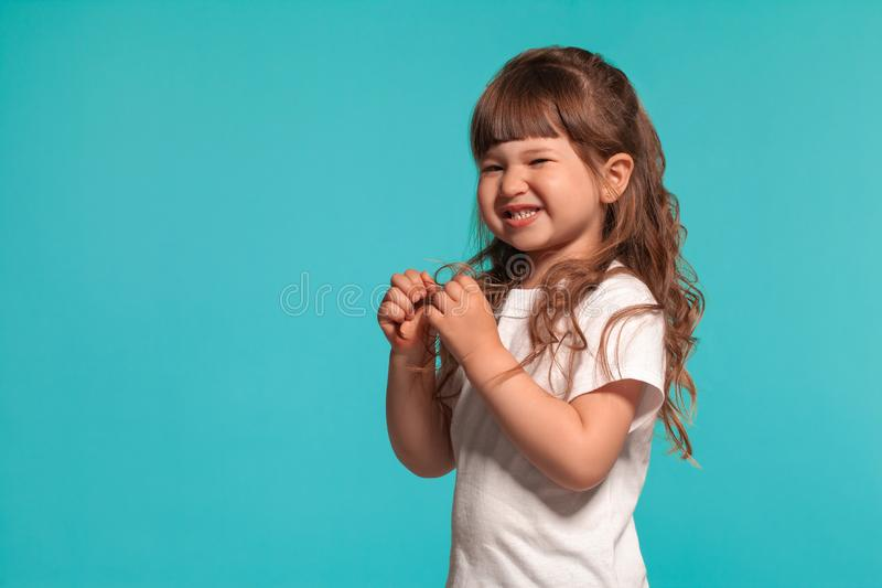 Beautiful little girl wearing in a white t-shirt is posing against a blue studio background. stock image