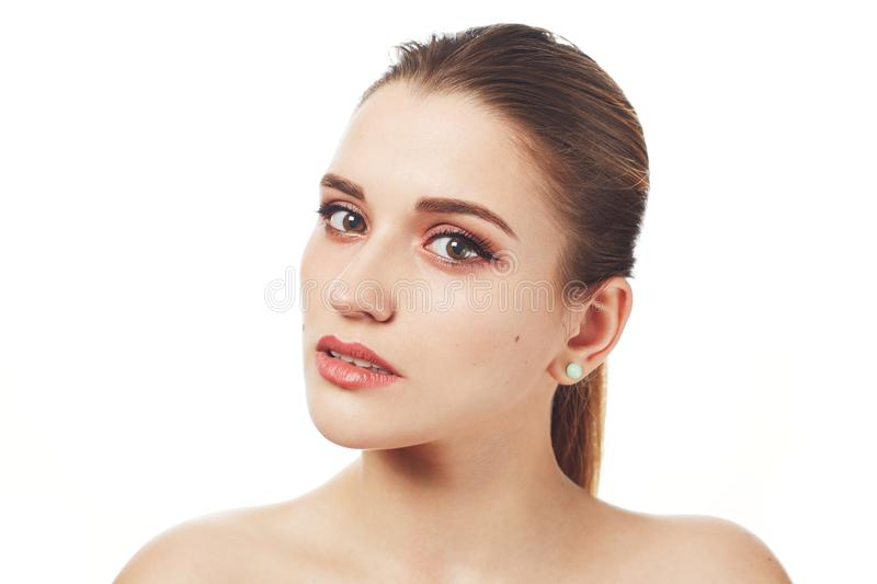 Close up shot of beautiful lovely young woman with make up and healthy pure skin poses against white studio background, demonstrat royalty free stock photos