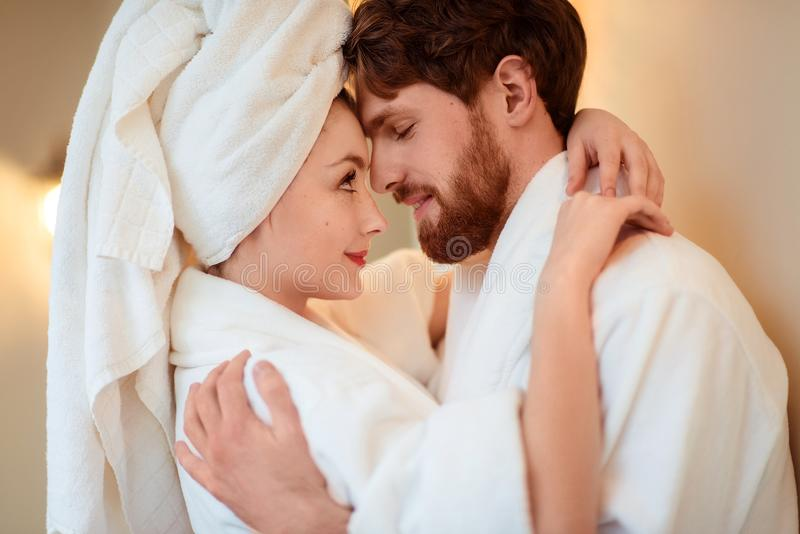 Close up shot of beautiful woman and her husband cuddle each other, express love, wear comfortable bathrobes, relax stock photography