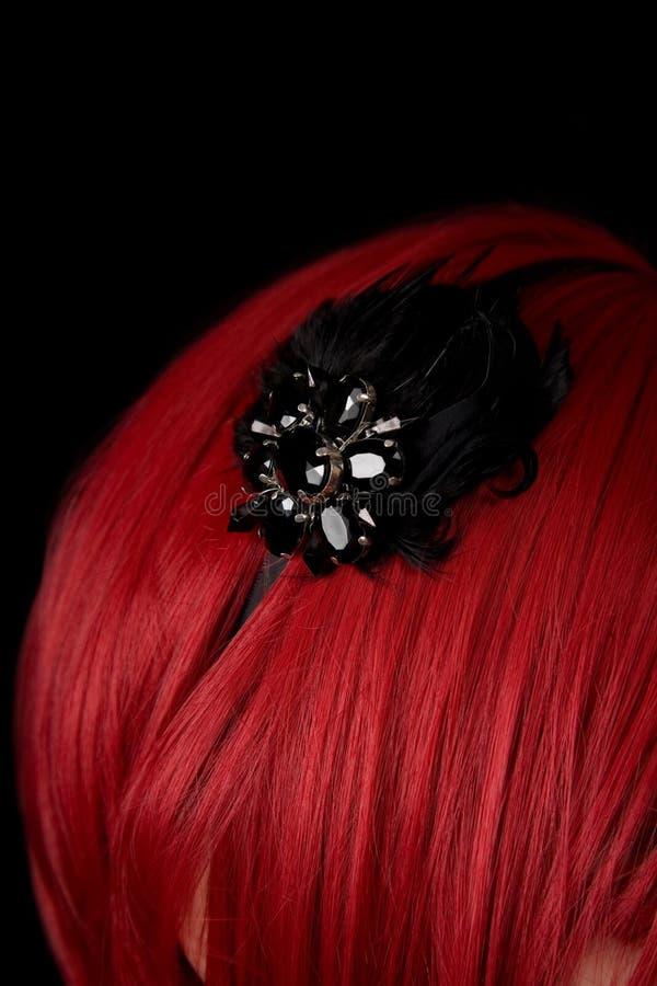 Close-up shot of black hair fascinator on red hair stock image