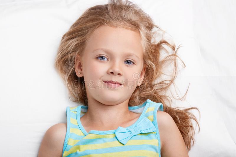 Close up shot of blue eyed small child looks pleasantly at camera, wears casual nightwear, has good rest in bed, being in good moo. D after having healthy sleep royalty free stock image