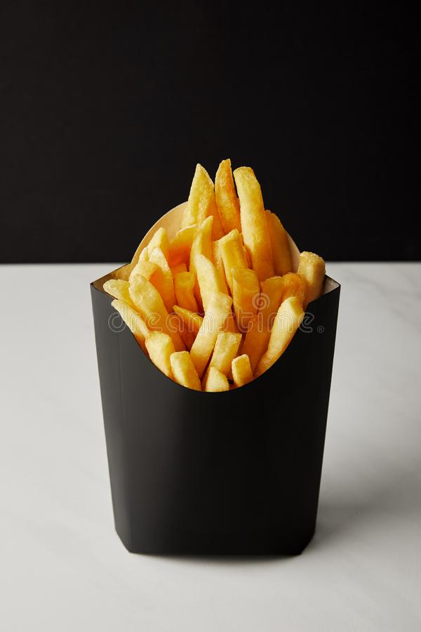 Close-up shot of box of french fries on white marble surface isolated on black royalty free stock photography