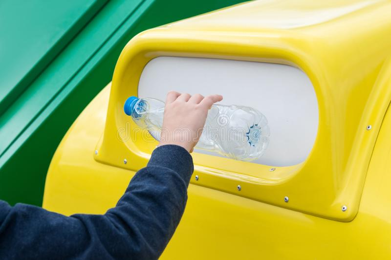 Close-up shot of a boy's hand throwing an empty plastic bottle into a separate garbage container stock photography