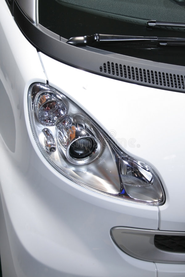 Close up shot of car. Head lamp of white smart car royalty free stock images