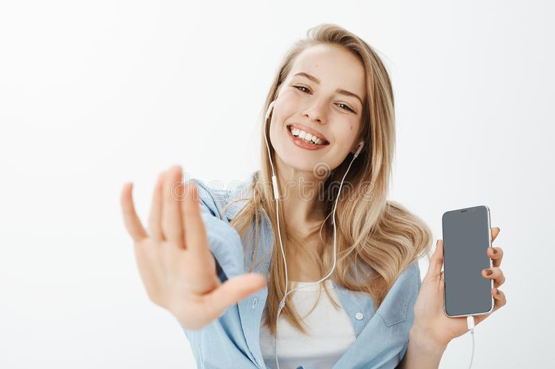 Close-up shot of carefree happy european girlfriend with fair hair, showing smartphone and pulling hand towards camera stock photography