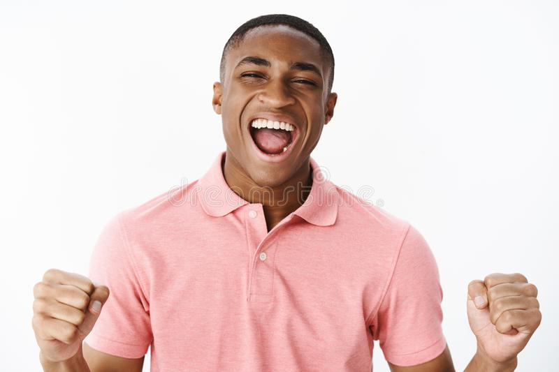 Close-up shot of charismatic over-emotive and excited young happy african american man clenching fists in joy and cheer stock images