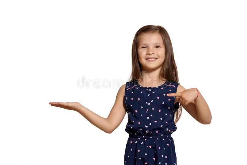 Close-up studio shot of beautiful brunette little girl posing isolated on white studio background. Close-up shot of charming brunette little kid wearing a blue royalty free stock images