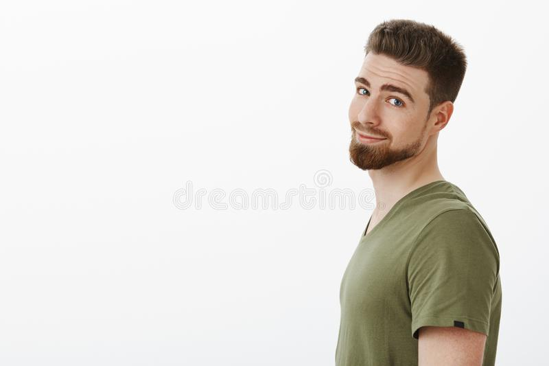 CLose-up shot of charming charismatic bearded boyfriend in t-shirt standing in profile turning head at camera and. Grinning delighted and carefree posing happy stock photography