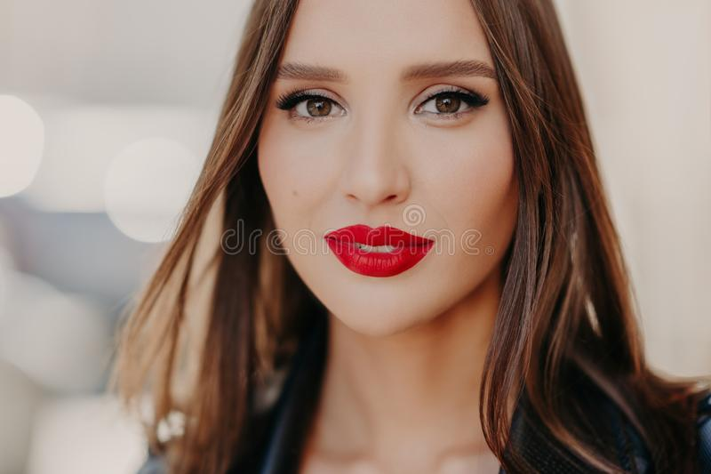 Close up shot of charming good looking European female with beautiful makeup, dark eyes wears red lipstick on lips, dressed in royalty free stock photos