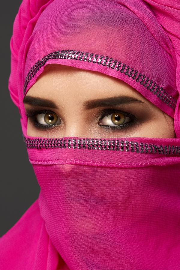 Close-up shot of a young charming woman wearing the pink hijab decorated with sequins. Arabic style. stock photography