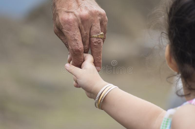 Close-up shot of a childs small hand holding finger of his father stock images