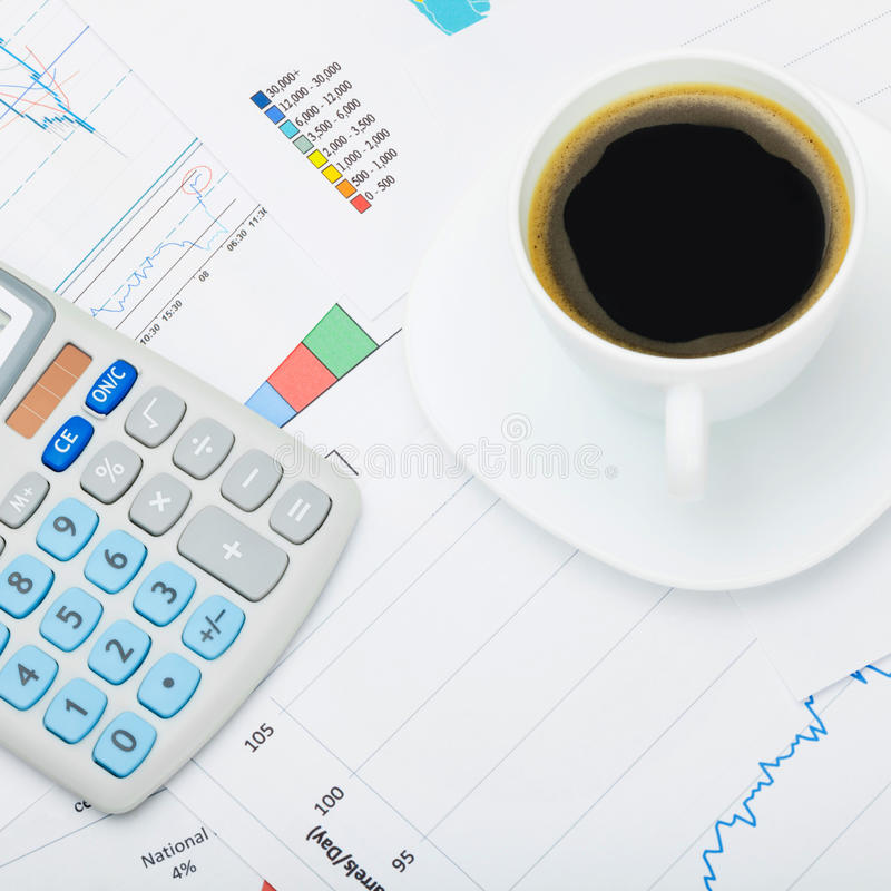 Close up shot of a coffee cup and calculator over world map and financial charts stock image