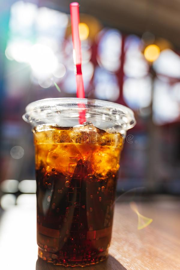 Close up shot of cold refreshing cola drink with ice and bubbles in plastic glass with red straw on wooden table with sun flare royalty free stock images