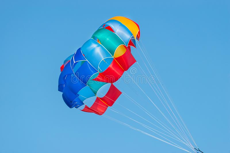 Close up shot of a colorful parachute used for parasailing pulled by a motorboat. stock images