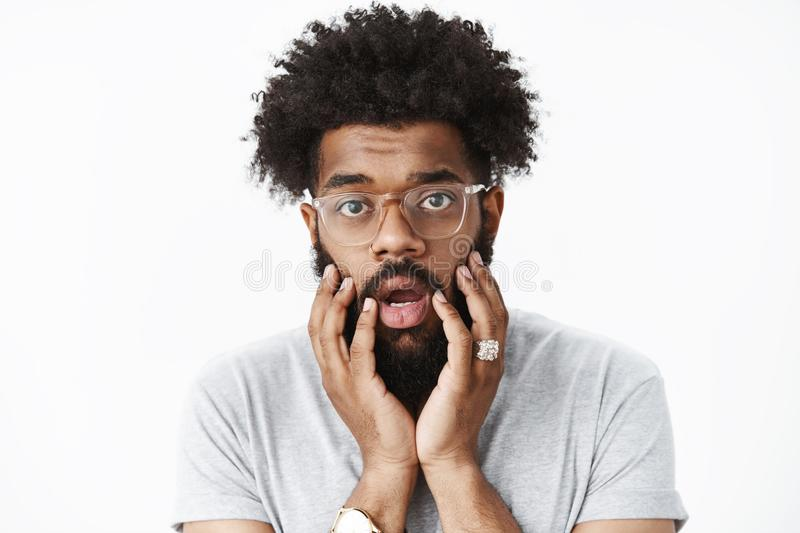 Close-up shot of concerned and worried adult african american bearded guy with afro hairstyle open mouth shook and stock image