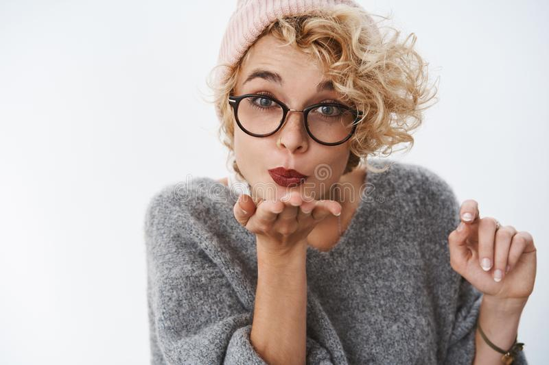 Close-up shot of cute beautiful blond curly-haired woman in glasses beanie and winter sweater sending warm kiss and stock photography