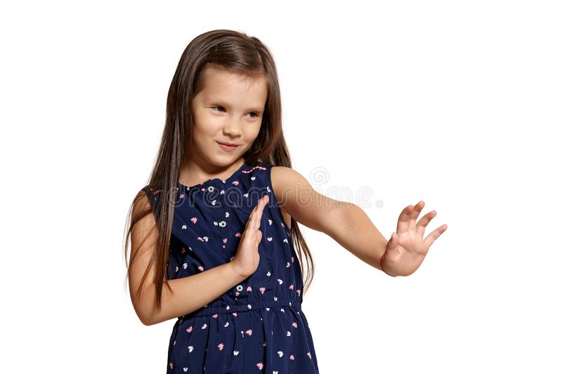 Close-up studio shot of beautiful brunette little girl posing isolated on white studio background. Close-up shot of cute brunette little kid wearing a blue suit stock photos