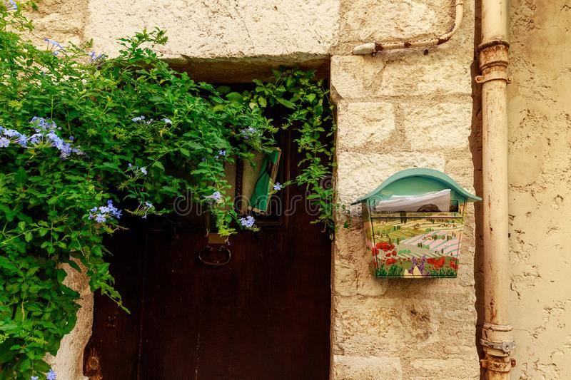 Close-up shot of door of ancient european building with wall covered with vine and decorated mailbox, Antibes, France. ANTIBES, FRANCE - 17 SEPTEMBER 2017: close royalty free stock photo
