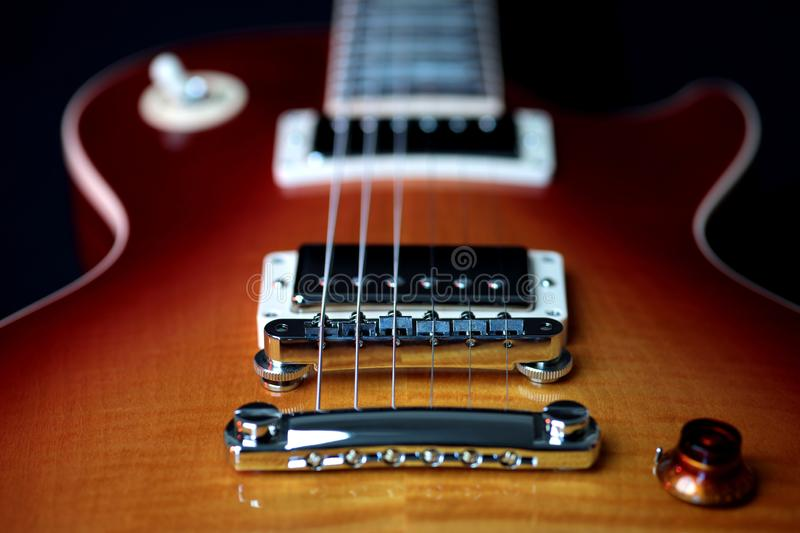 Electric Guitar Bridge Pick Up, Tailpiece and Strings. Close up shot of an electric guitar body, bridge pick up, tailpiece and strings stock photo