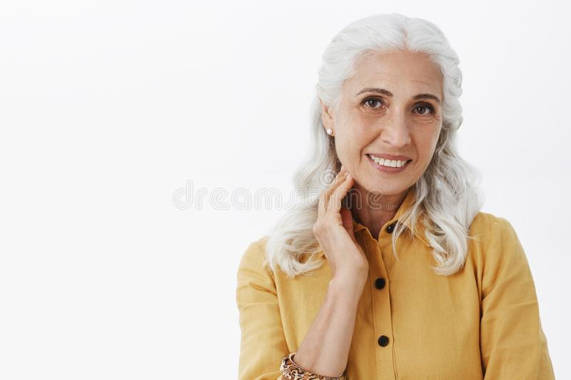 Close-up shot of elegant energized and healthy senior lady in trendy yellow coat and earrings touching clean and healthy royalty free stock photo